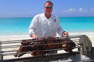 whole barbeque pig on spit with chef