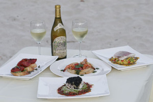 bottle of wine and food served on beach